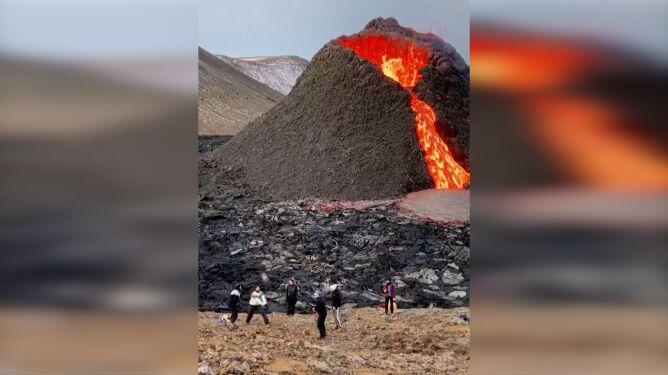 Grali w siatkówkę obok tryskającego lawą wulkanu